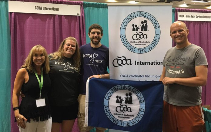 adrian bailey with two others CODA international banner